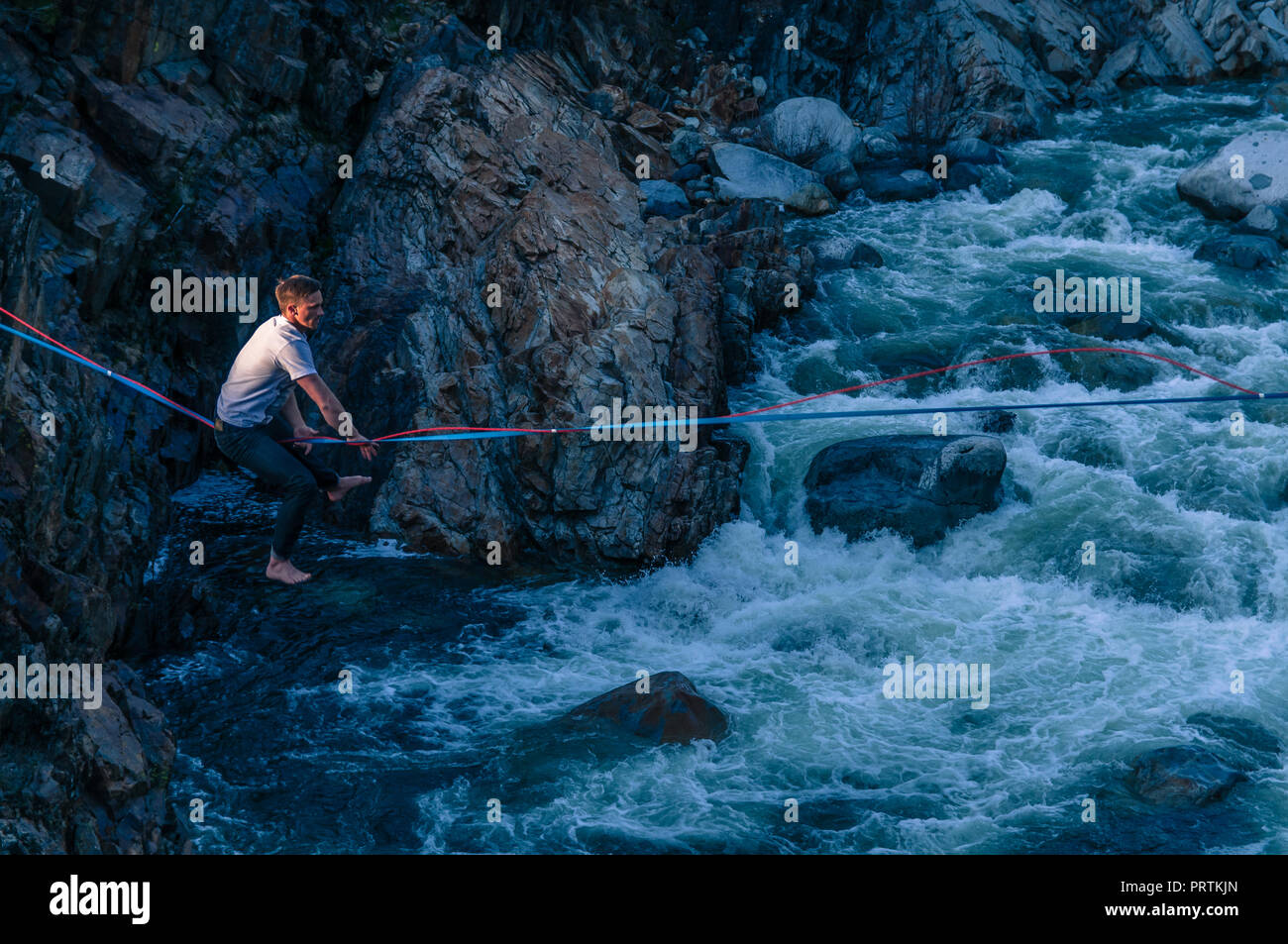 Man highlining above river, Truckee, California, USA - Stock Image