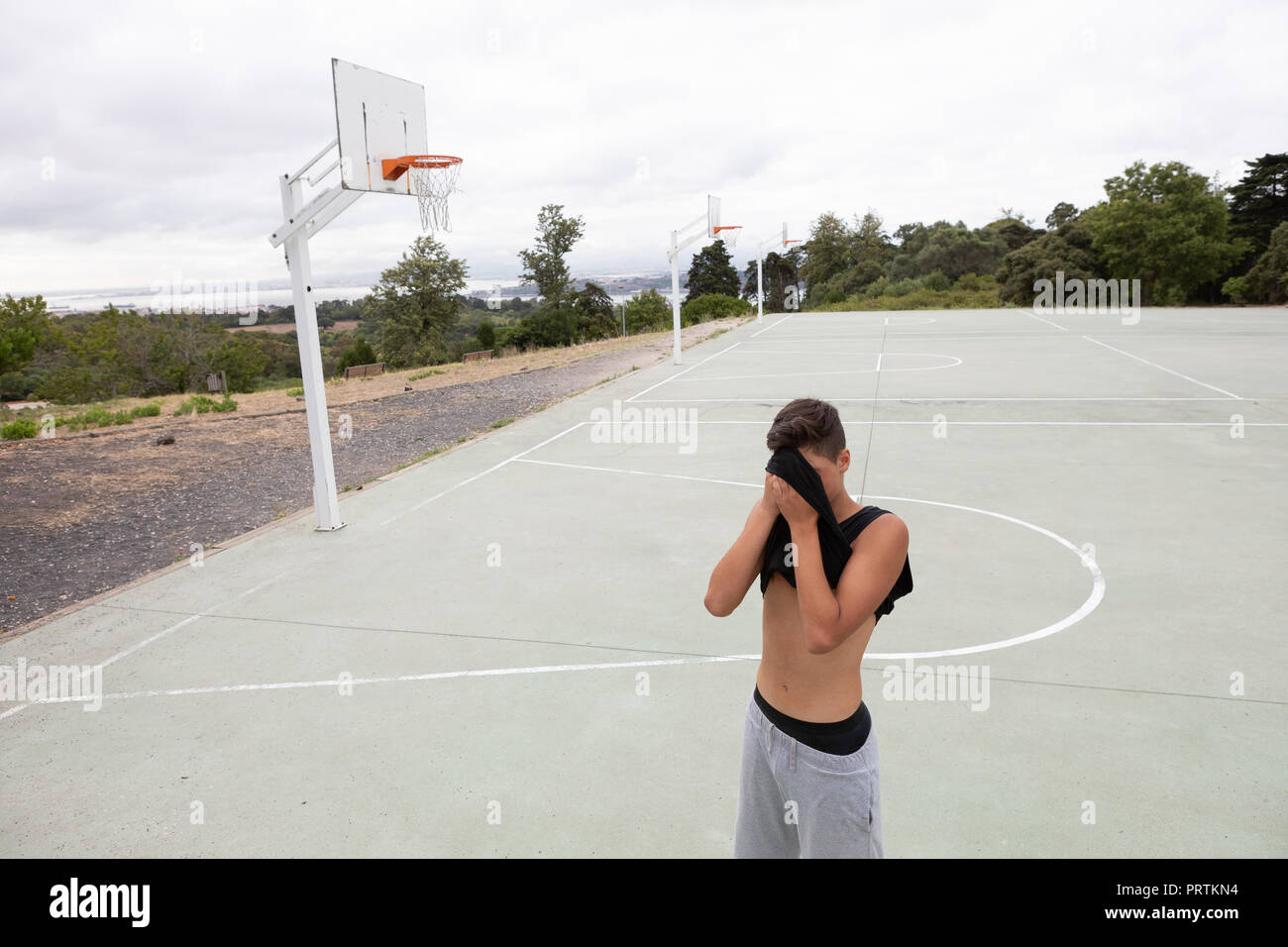 Male teenage basketball player wiping his brow with vest on basketball court - Stock Image