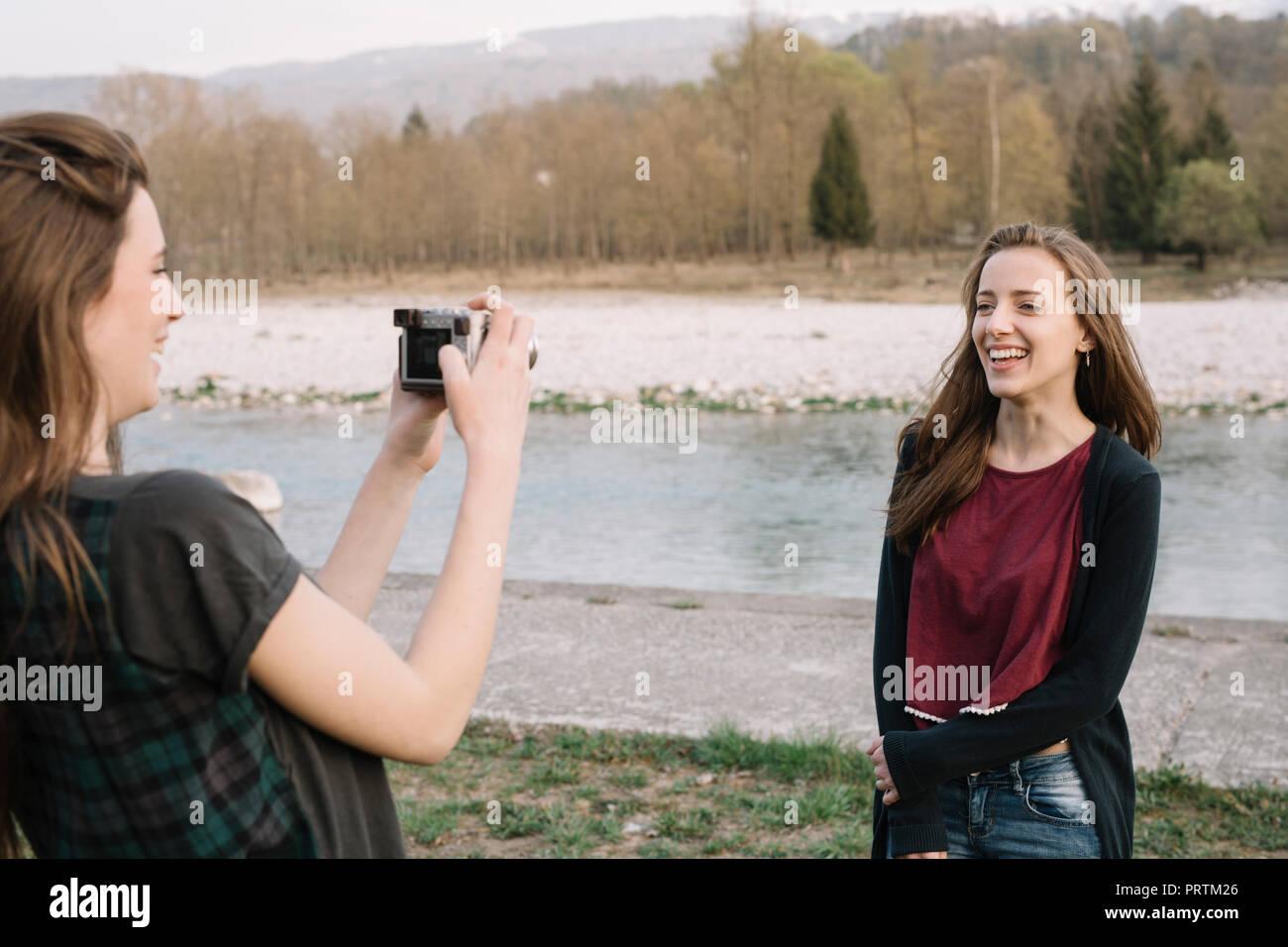 Girlfriends taking photograph by river, Belluno, Veneto, Italy - Stock Image