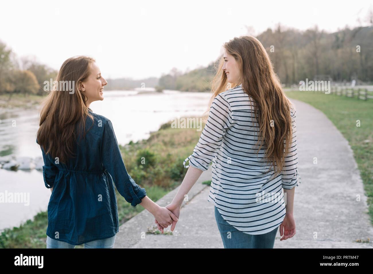 Girlfriends taking walk by river, Belluno, Veneto, Italy - Stock Image