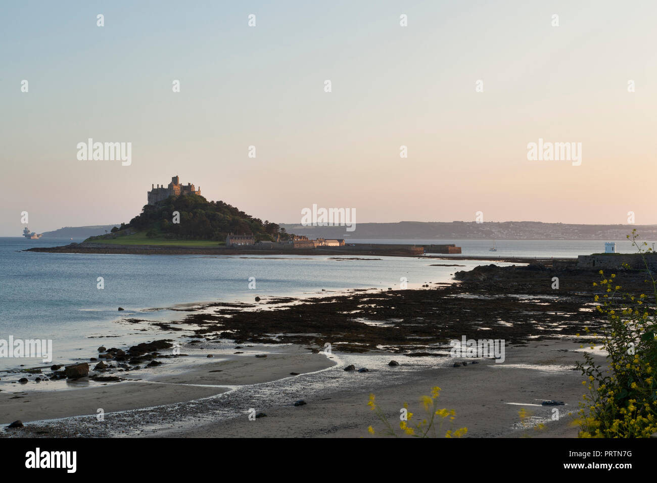 Mount's Bay beach and St. Michael's Mount, with HMS Queen Elizabeth aircraft carrier ship is distance, Cornwall, UK - Stock Image