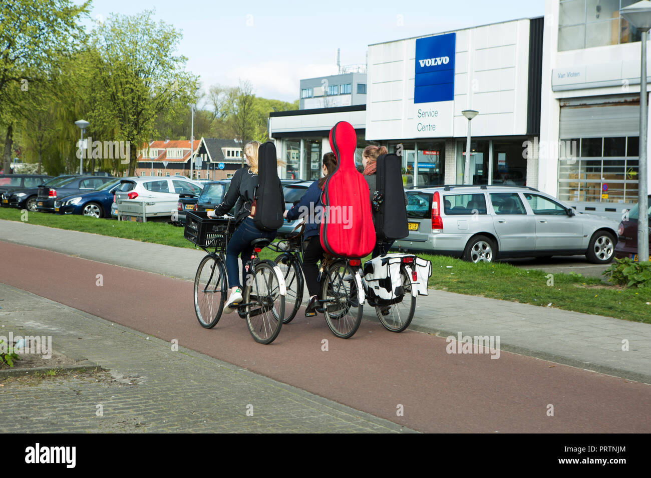 Three cyclists carrying violin and cello cases cycling past a Volvo dealership sign. Amsterdam. The Netherlands. - Stock Image