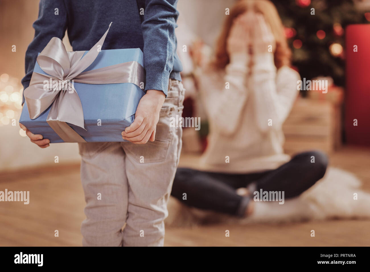 Rear view of unpredictable present for mother - Stock Image