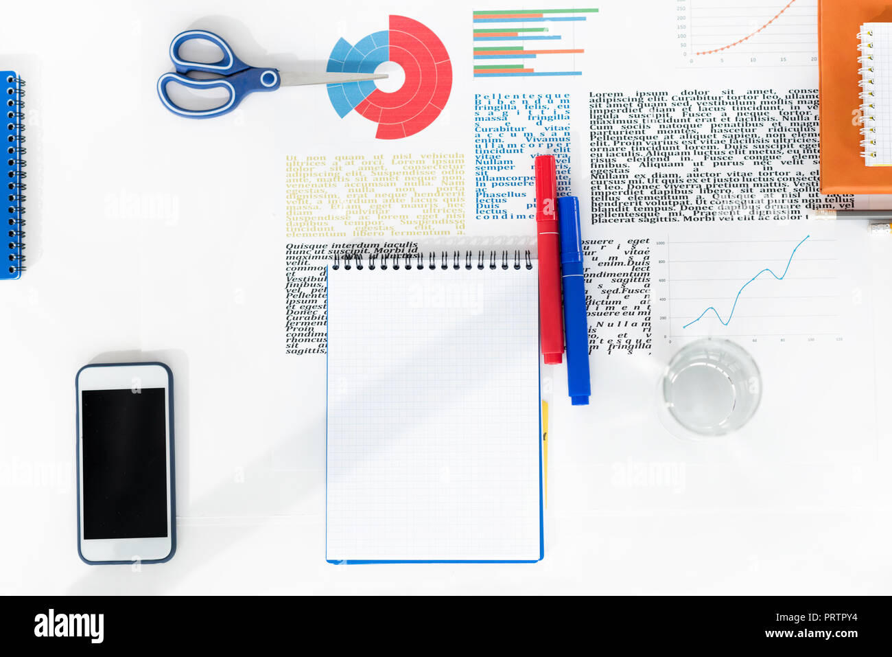 Top view of smartphone with blank screen, empty notebook with markers, scissors and business charts at workplace - Stock Image