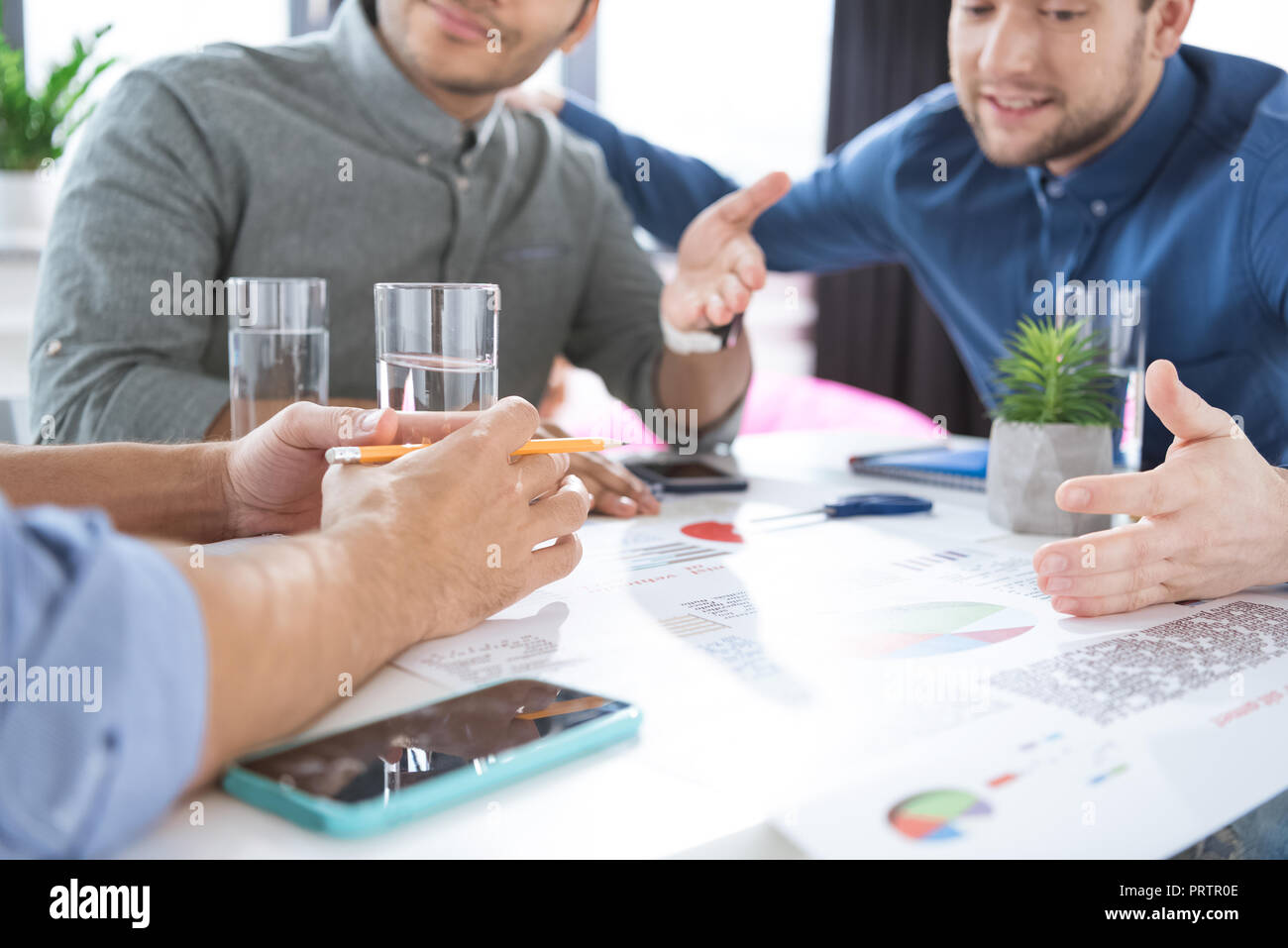 Smiling young businessmen drinking water and discussing new project, business teamwork concept - Stock Image