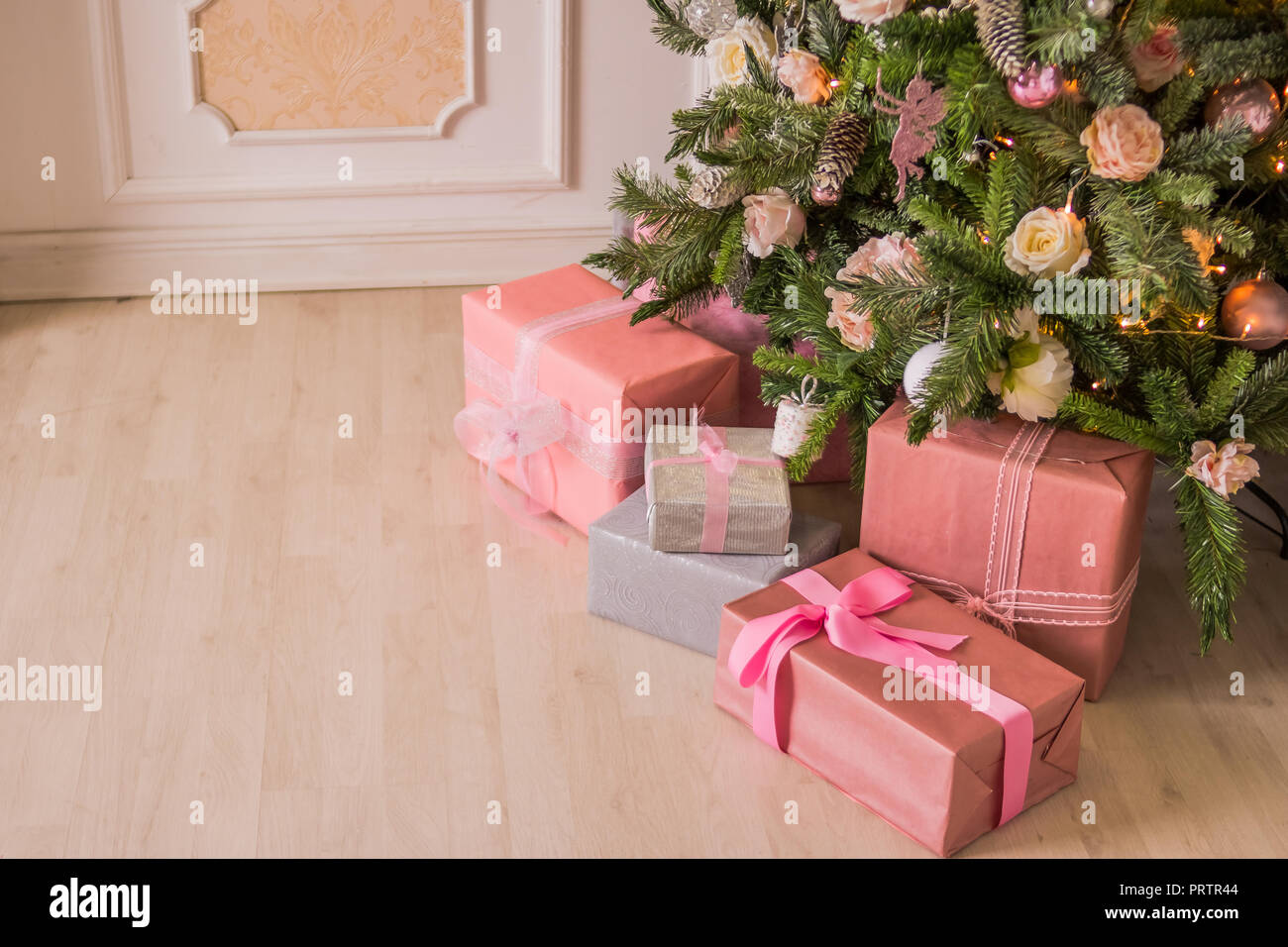 pastel christmaselegant christmas tree with decorations and gifts on elegant hardwood floor pink christmas gift boxes with pink and silver ribbon next to