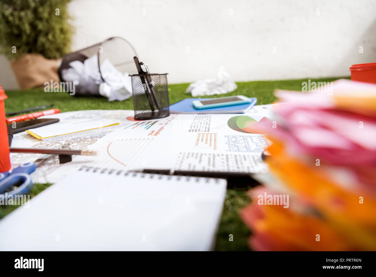 heap of business objects and office supplies laying on green grass carpet at office, business establishment - Stock Image