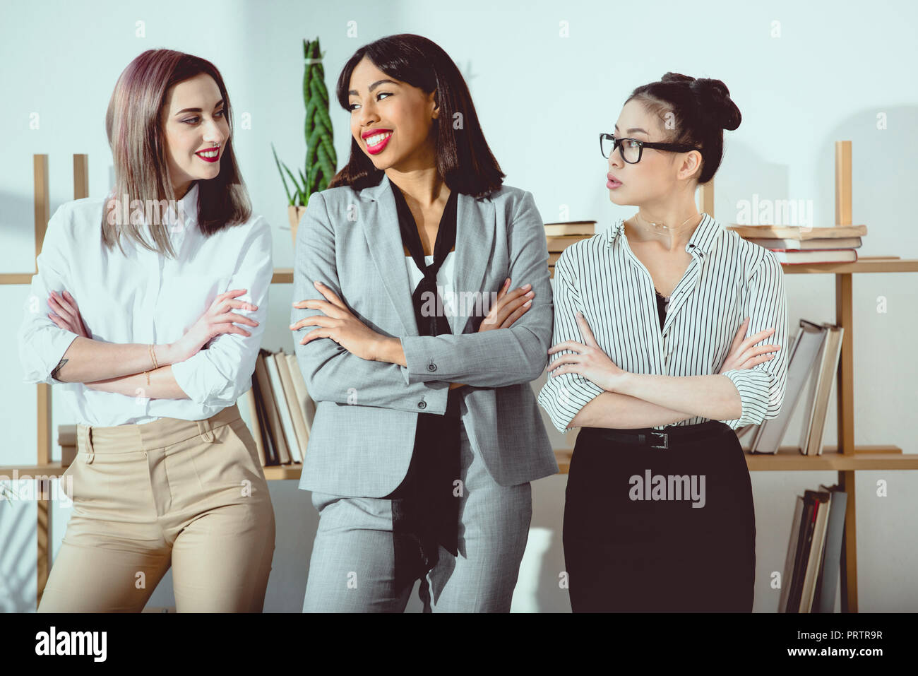 smiling multiethnic businesswomen in formal wear standing with arms crossed - Stock Image