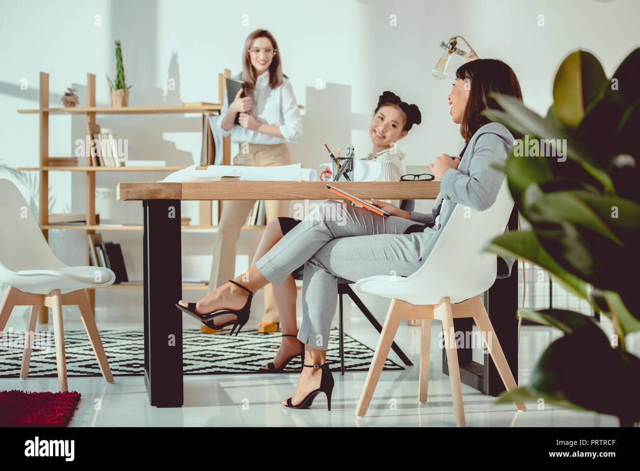 young multiethnic businesswomen in formal wear working together at office - Stock Image