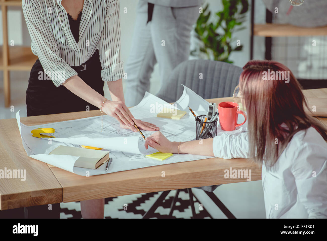 cropped shot of designers in formal wear working with blueprints at office - Stock Image