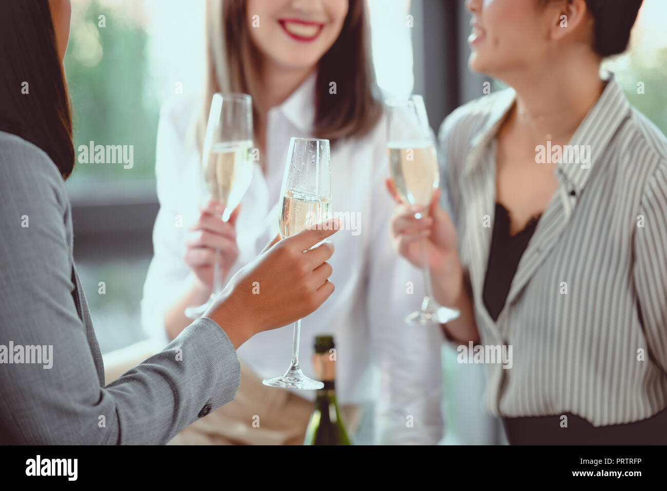 cropped shot of businesswomen in formal wear drinking champagne indoors Stock Photo