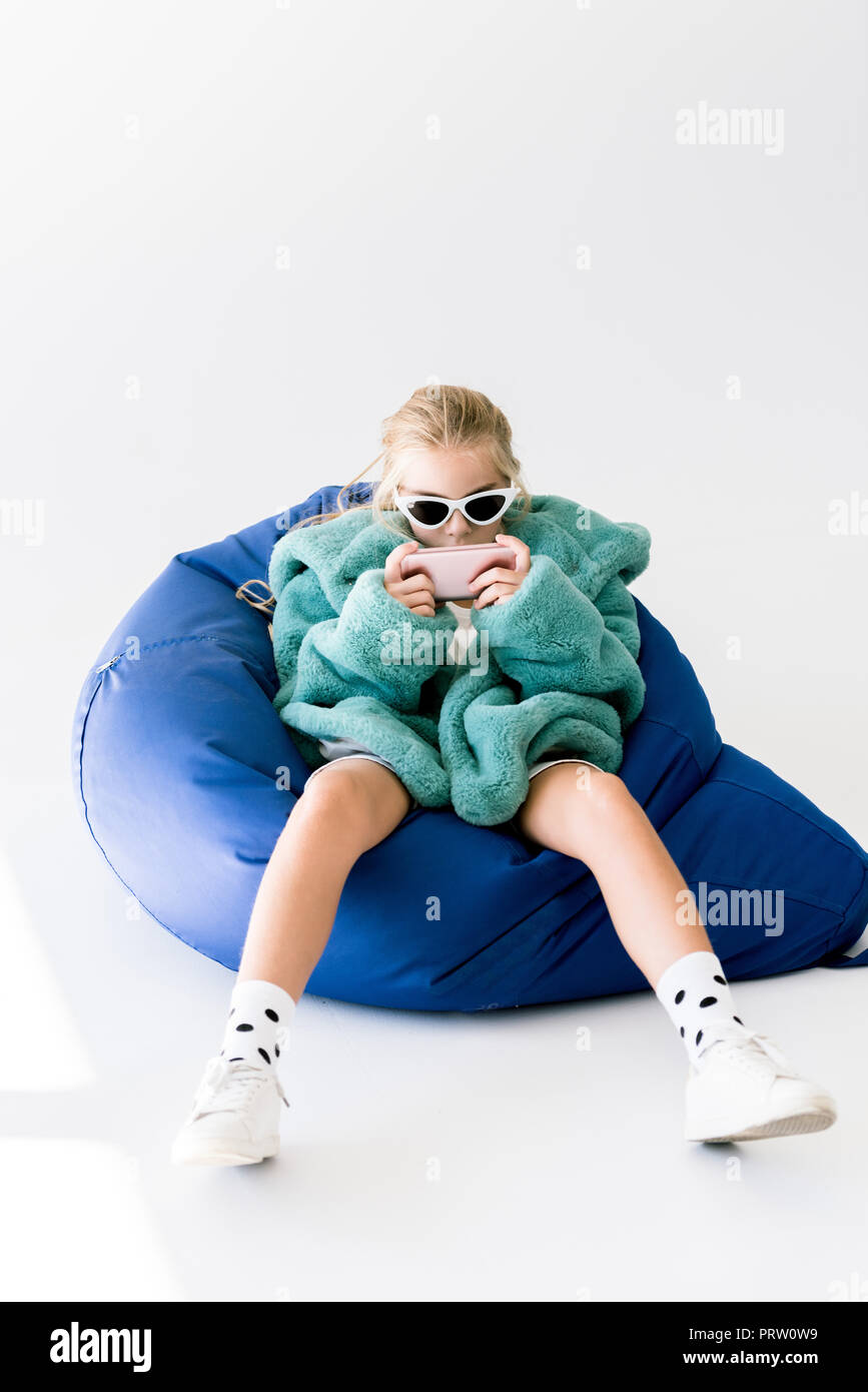 fashionable kid in fur coat and sunglasses using smartphone while sitting in bean bag chair on white - Stock Image