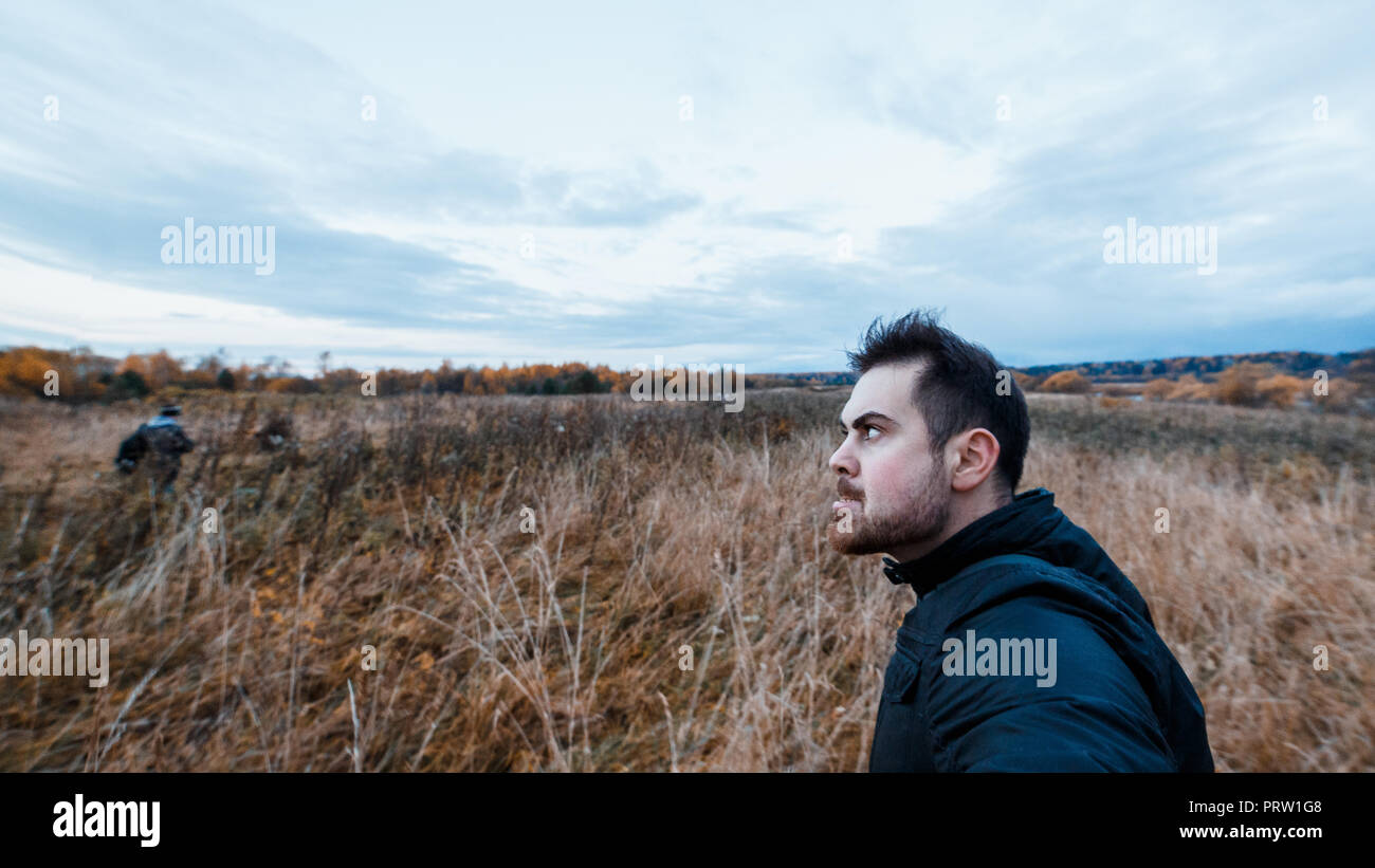 Man with a manic expression in black jacket stalking the victim in the autumn forest. Concept of autumn aggravation in mentally ill people. Stock Photo