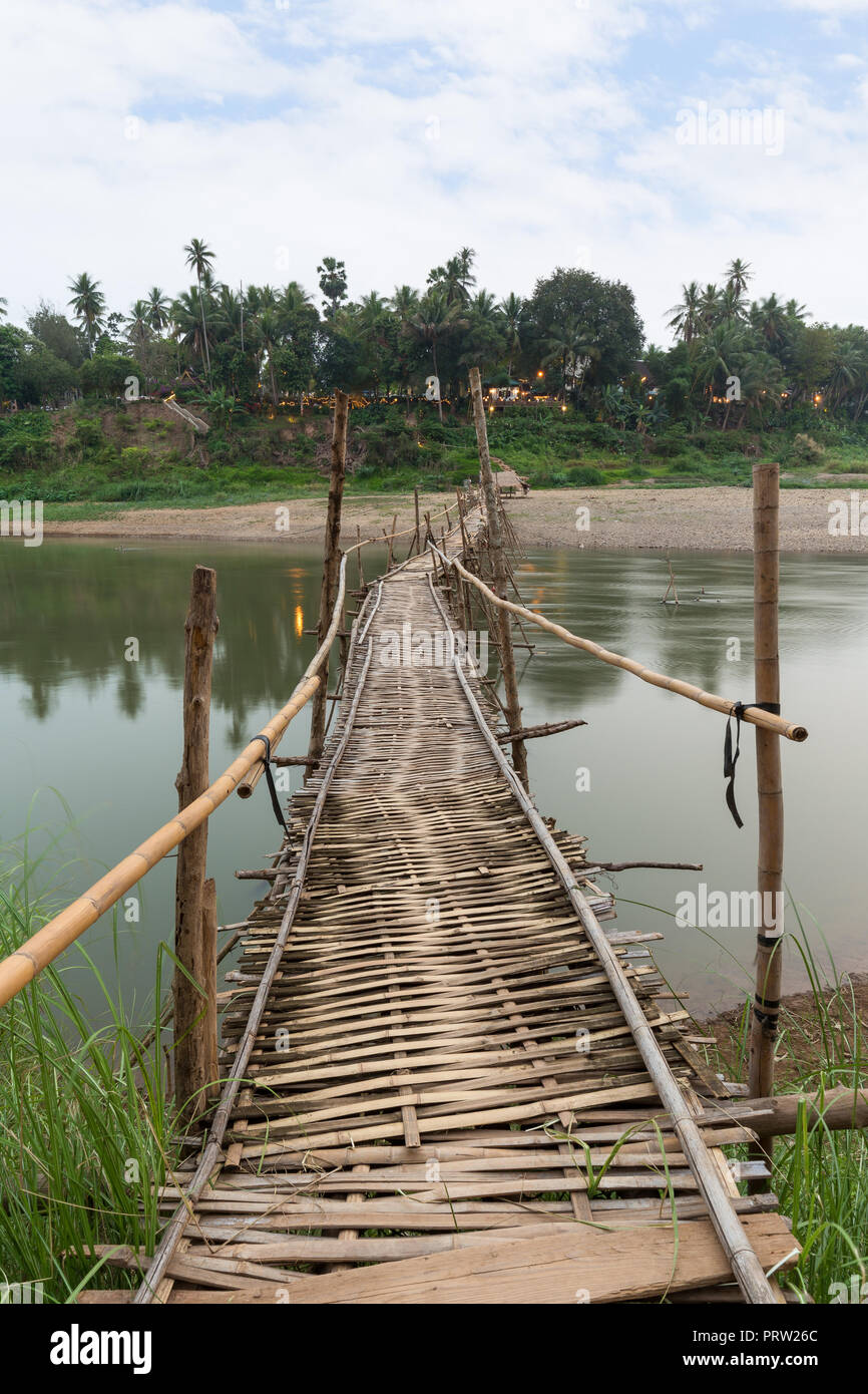 Wooden bamboo bridge over Nam Khan River at low tide viewed from the front in Luang Prabang, Laos. - Stock Image