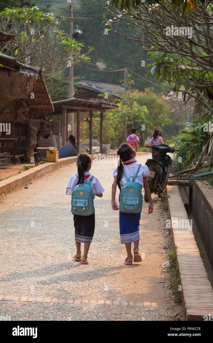 Two young schoolgirls wearing school uniforms walking on a small street and going home after school in the Chompet district in Luang Prabang, Laos. - Stock Image