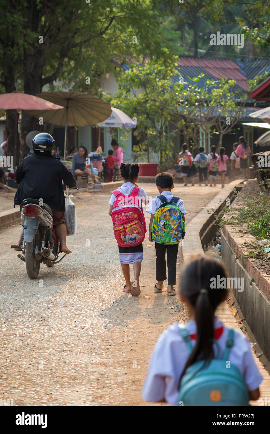 Several young schoolchildren wearing school uniforms walking on street and going home after school in the Chompet district in Luang Prabang, Laos. - Stock Image