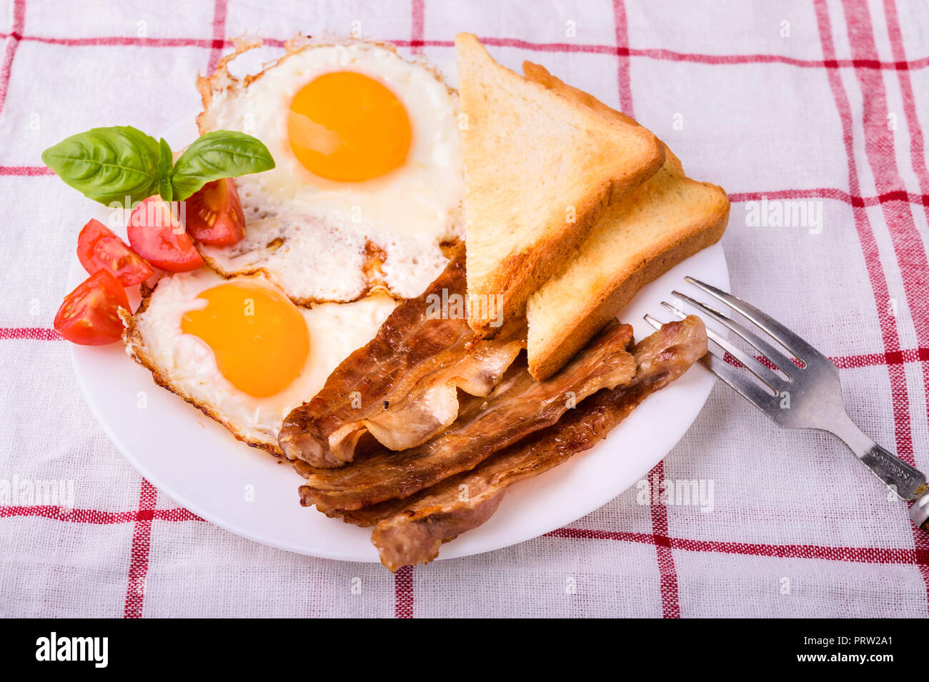 Breakfast with bacon and fried eggs. Served on white plate with sliced cherry tomato, basil leaves and crispy toast slice. Stock Photo