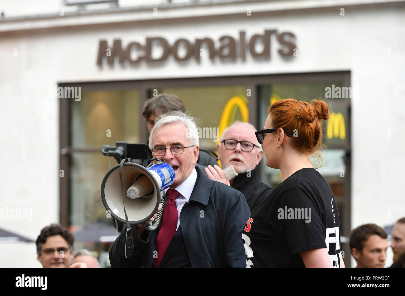 Shadow chancellor John McDonnell speaking at a rally about disputes over pay and union recognition in Leicester Square, London. - Stock Image