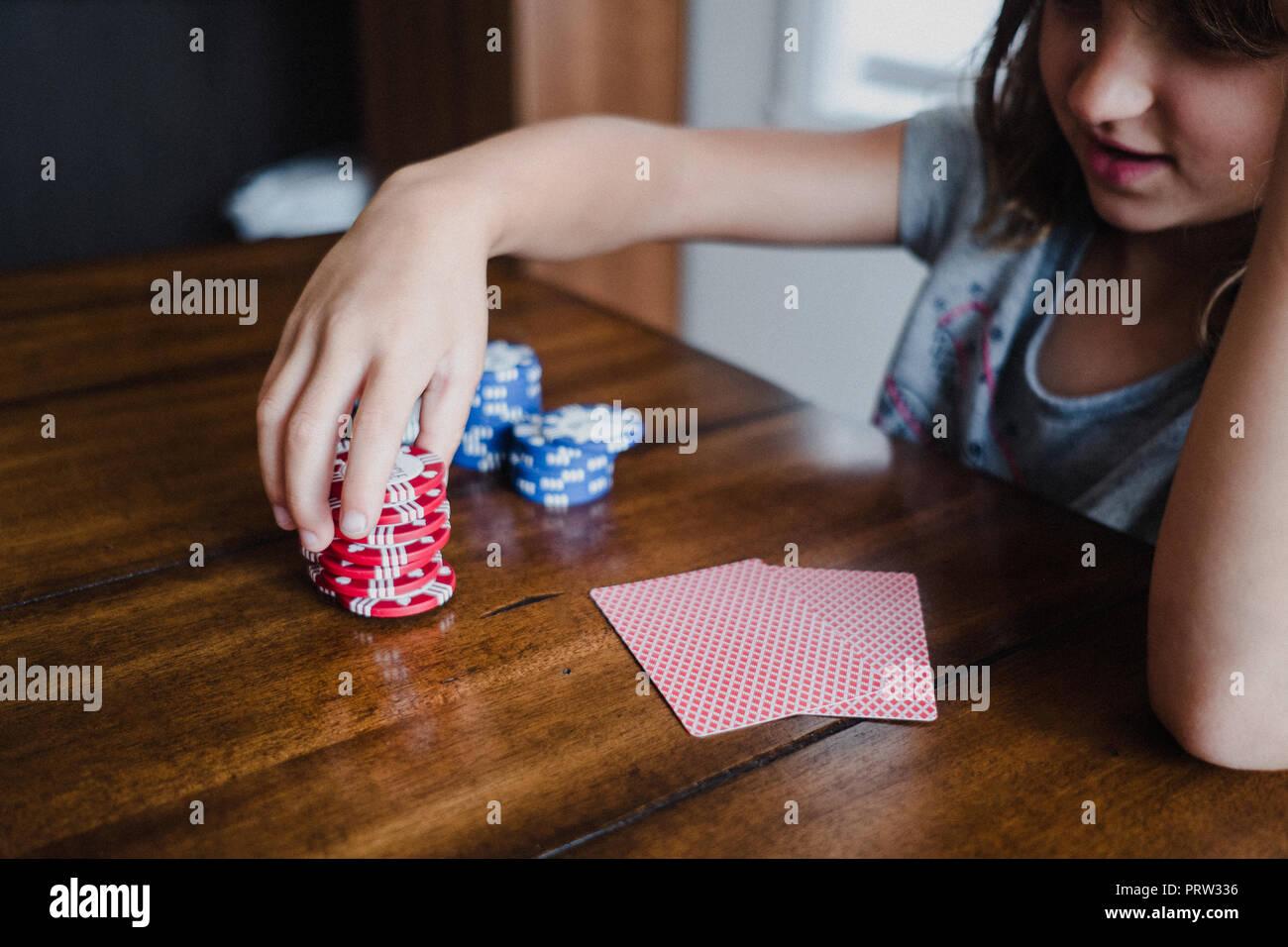 Girl playing cards at table, stacking gambling chips, close up - Stock Image