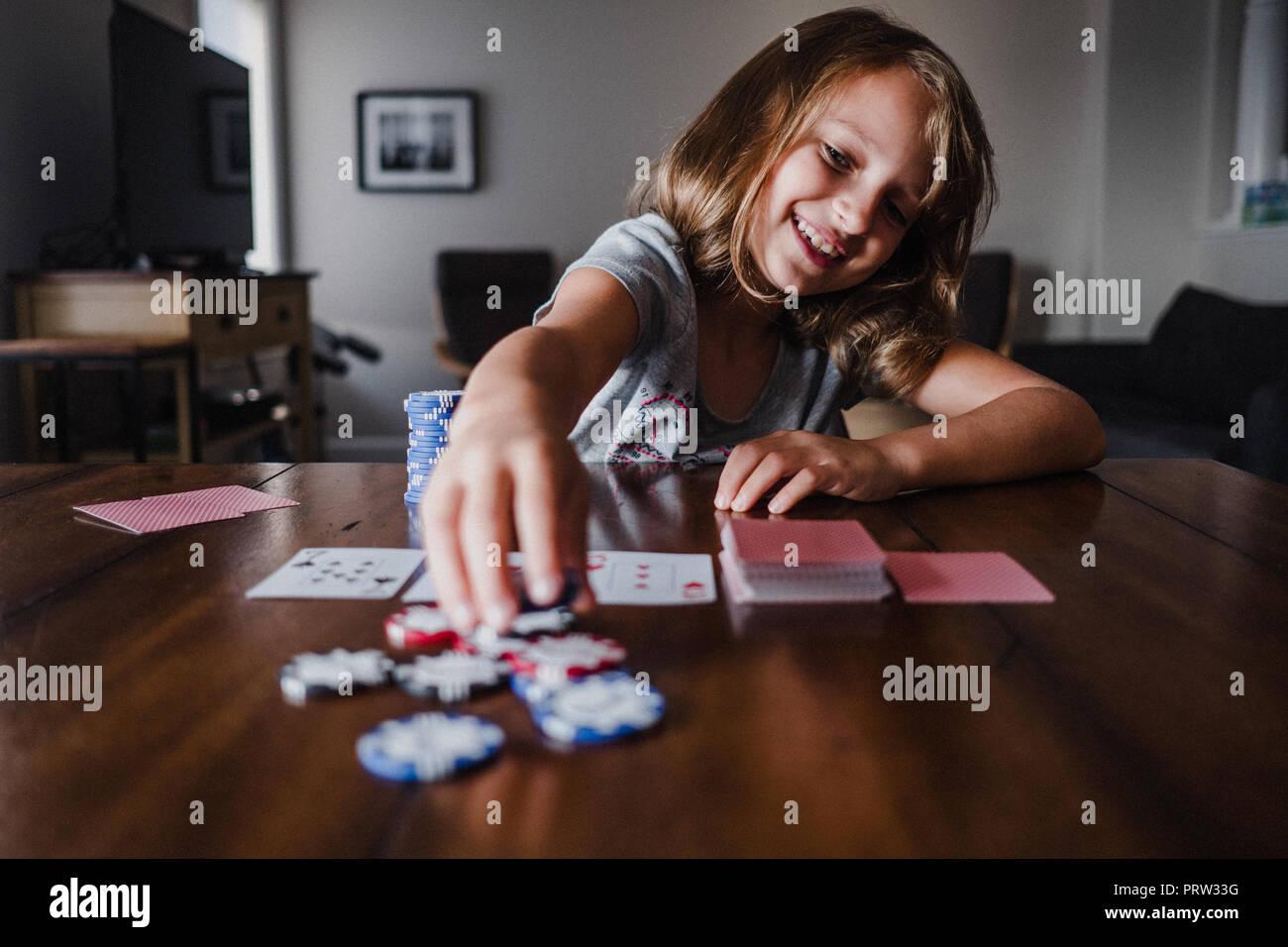 Girl playing cards at table, placing gambling chips - Stock Image