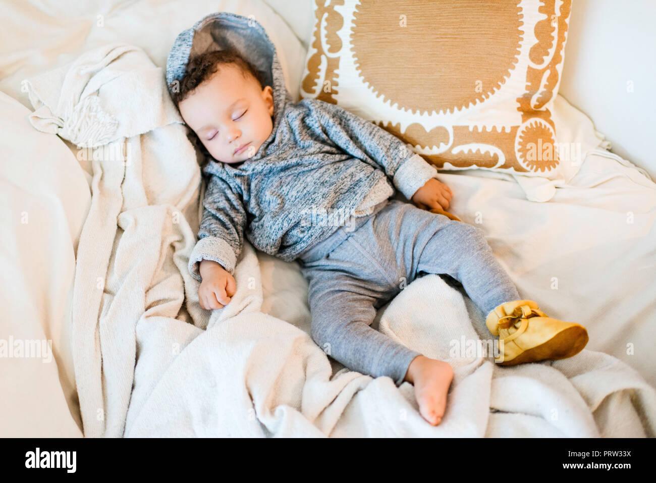Baby boy wearing hoody asleep on blanket - Stock Image