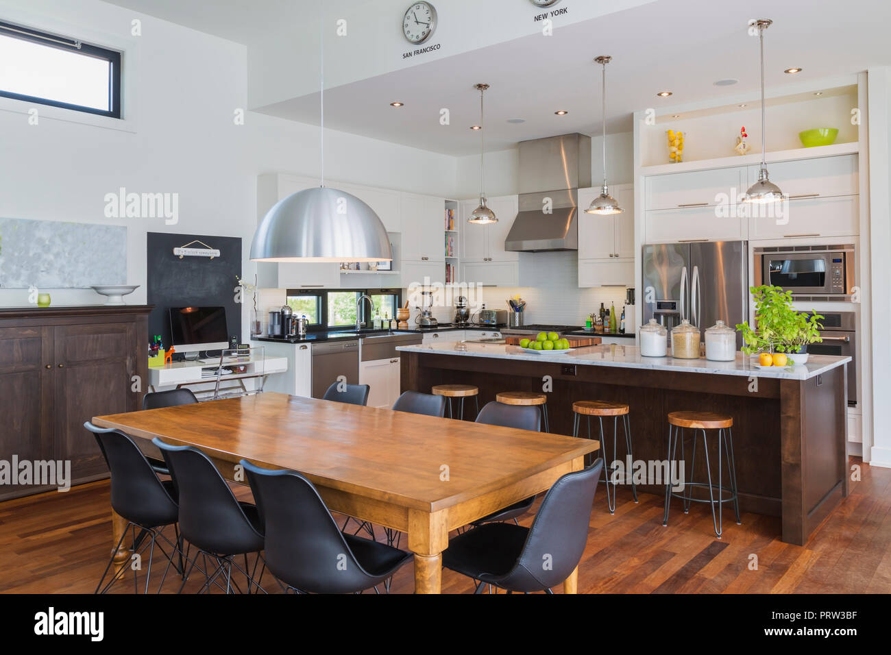 Open plan kitchen dining area with antique table, marble top kitchen island in luxurious modern cube style house interior Stock Photo