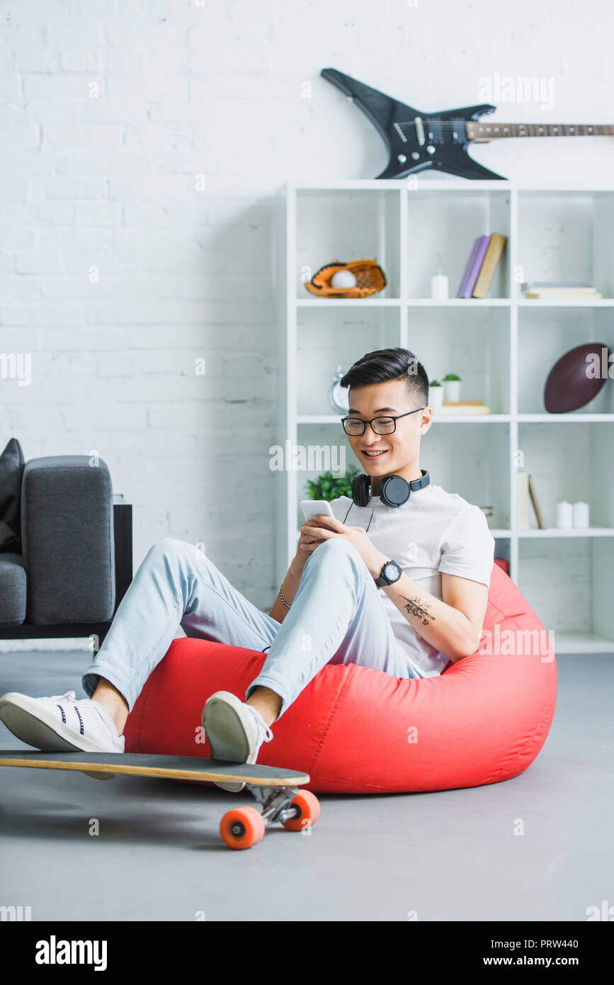 Admirable Smiling Young Asian Man Sitting In Bean Bag Chair And Using Pabps2019 Chair Design Images Pabps2019Com