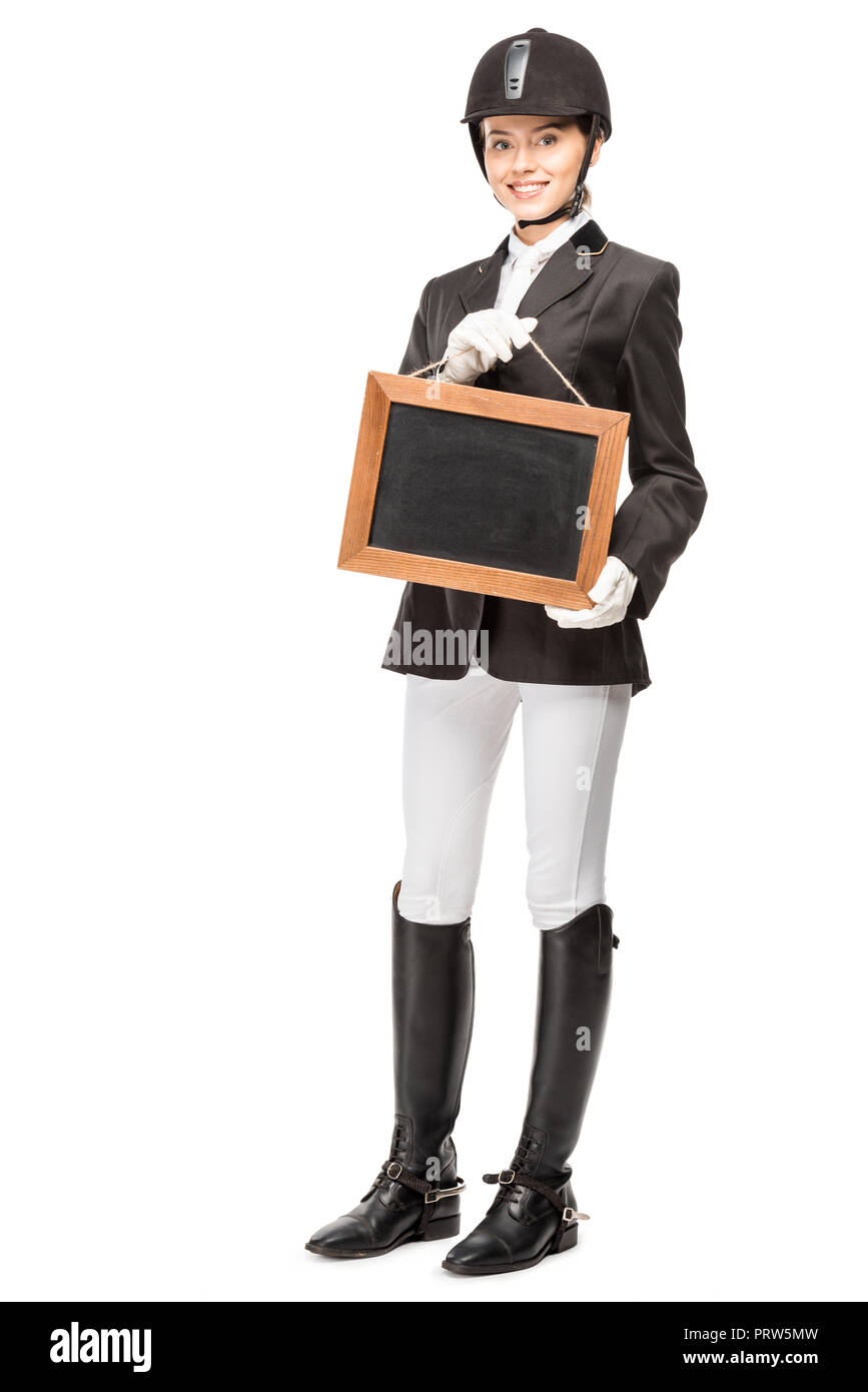 beautiful young horsewoman in uniform holding blank chalkboard isolated on white - Stock Image