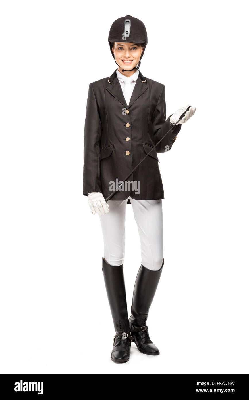 smiling young horsewoman in uniform holding horseman stick isolated on white - Stock Image