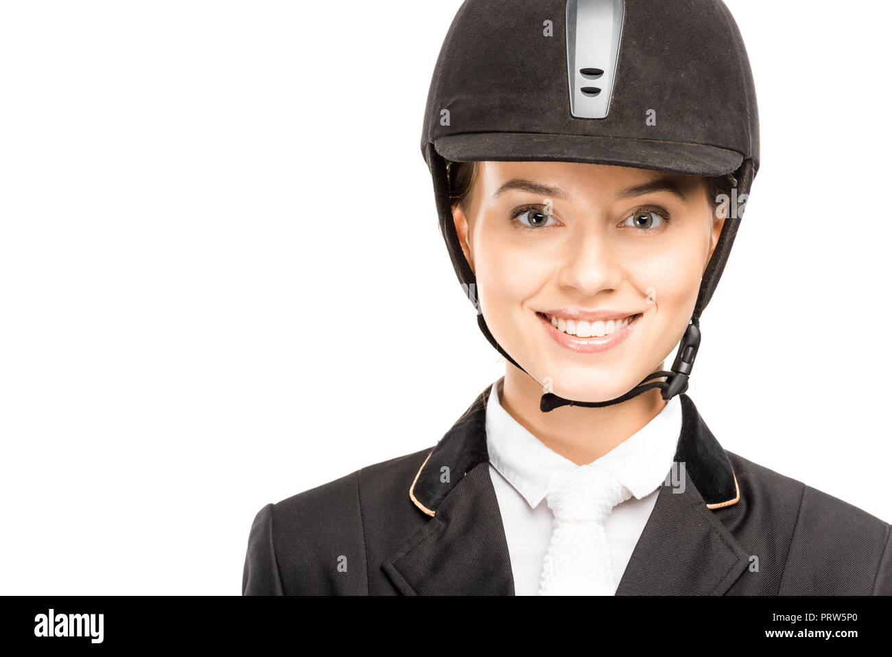 close-up portrait of happy young horsewoman in helmet looking at camera isolated on white - Stock Image