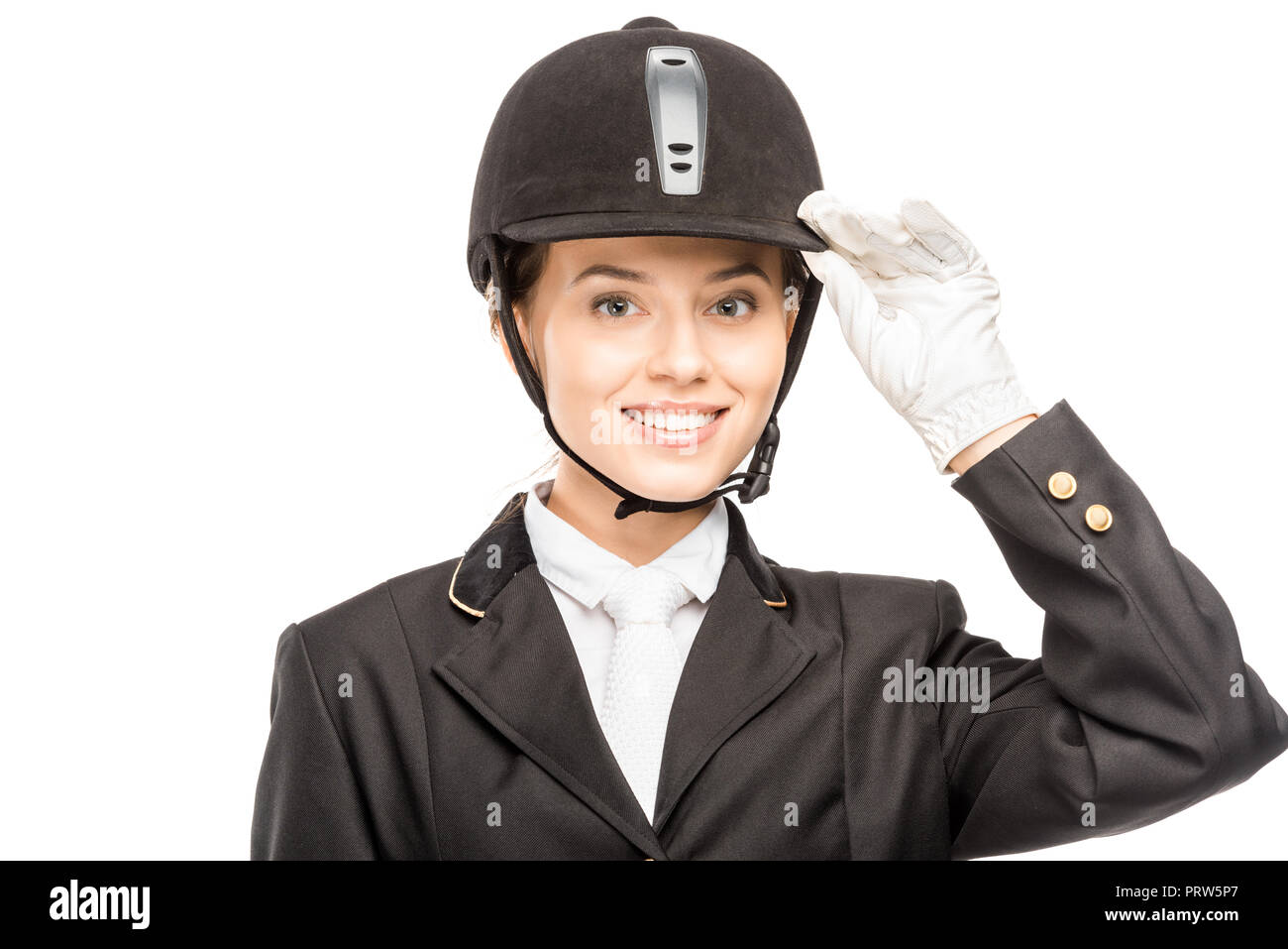 close-up portrait of smiling young horsewoman in safety helmet looking at camera isolated on white - Stock Image