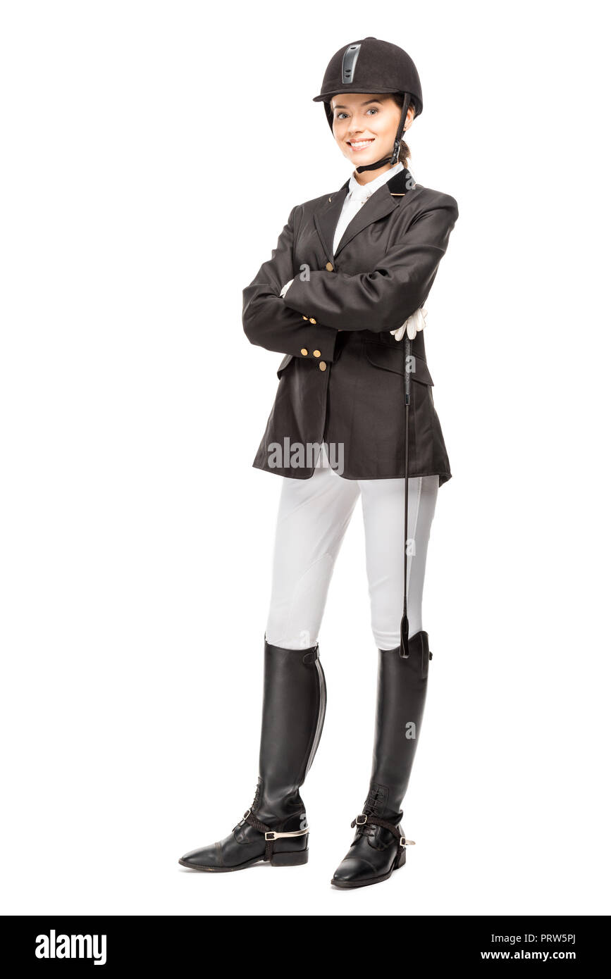 happy young horsewoman in uniform holding horseman stick and looking at camera isolated on white - Stock Image
