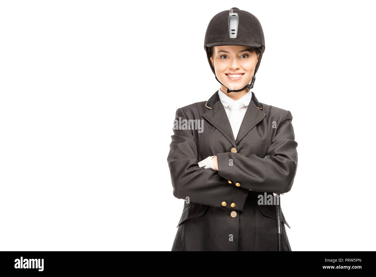 happy young horsewoman in uniform and helmet looking at camera with crossed arms isolated on white - Stock Image