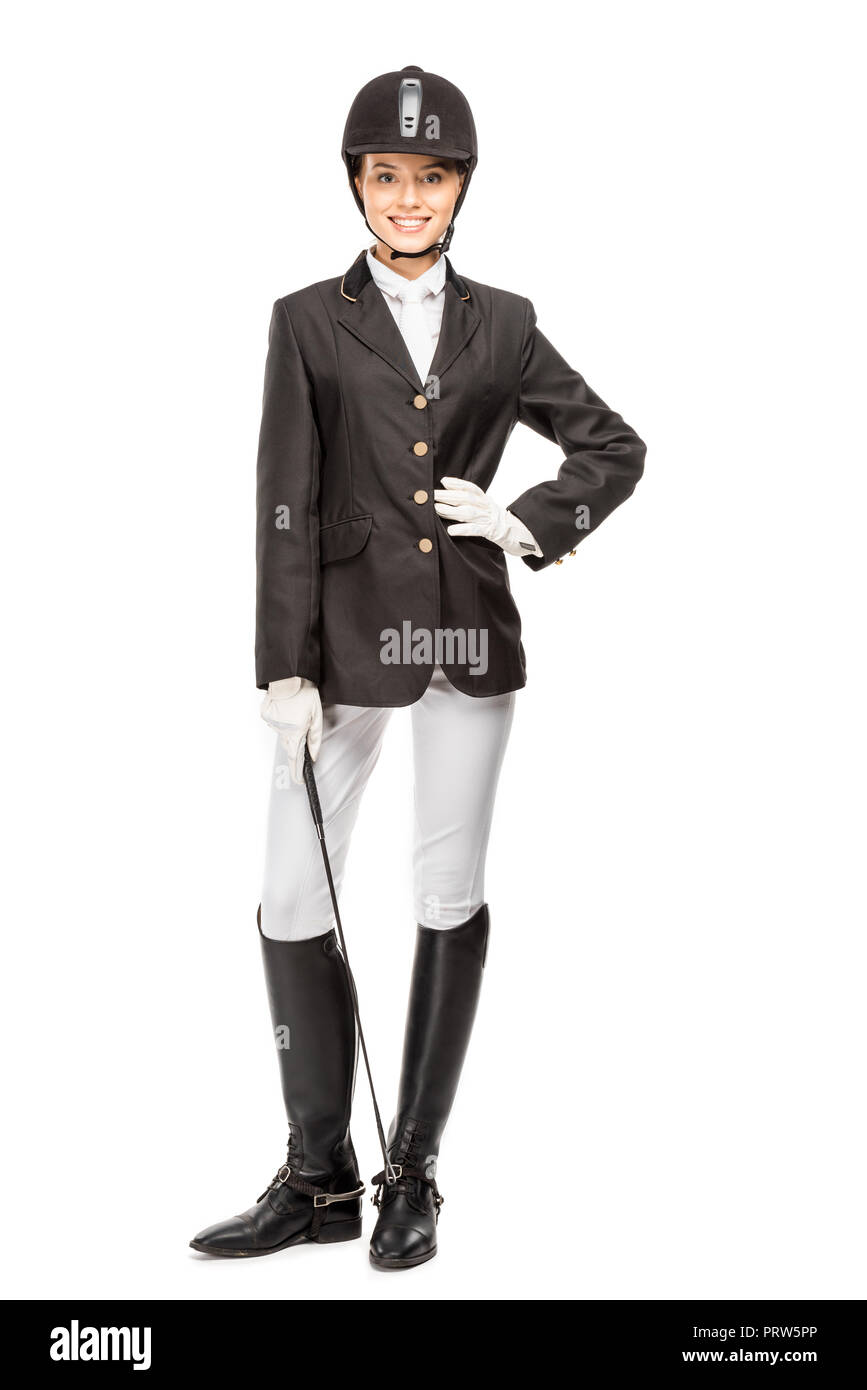 smiling young horsewoman in uniform holding horseman stick and looking at camera isolated on white - Stock Image