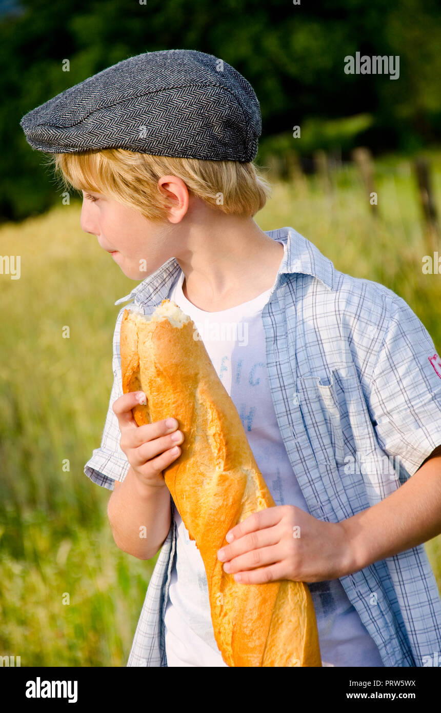 boy with bread in a wheat field Stock Photo