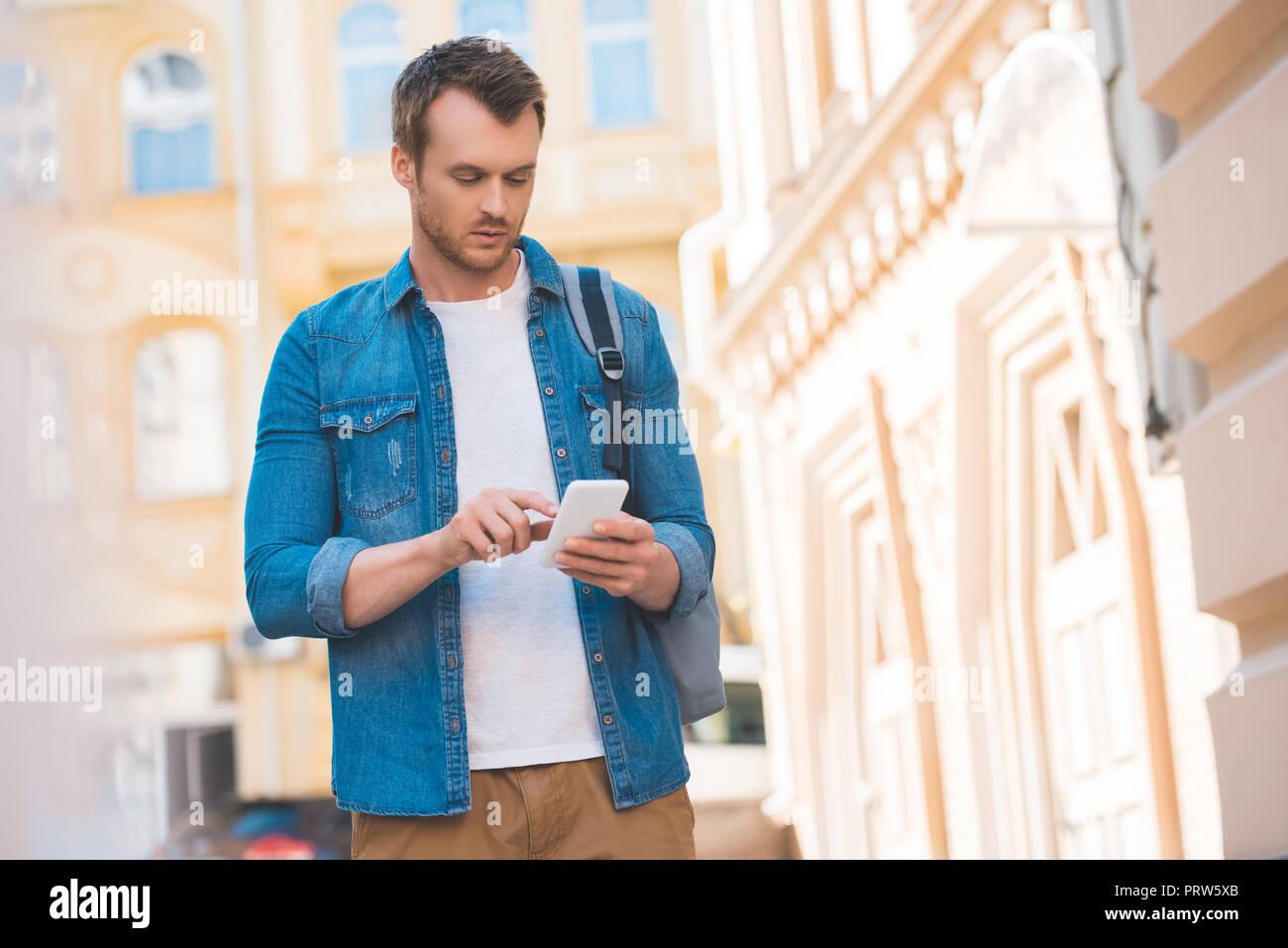portrait of focused man in denim shirt using smartphone on street - Stock Image