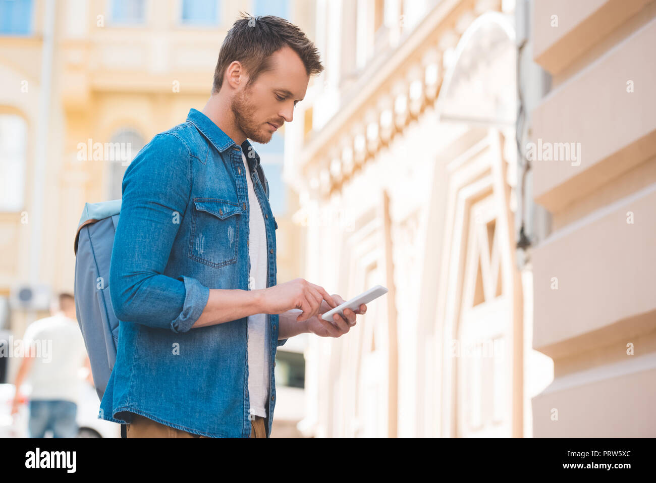 side view of man in denim shirt using smartphone on street - Stock Image