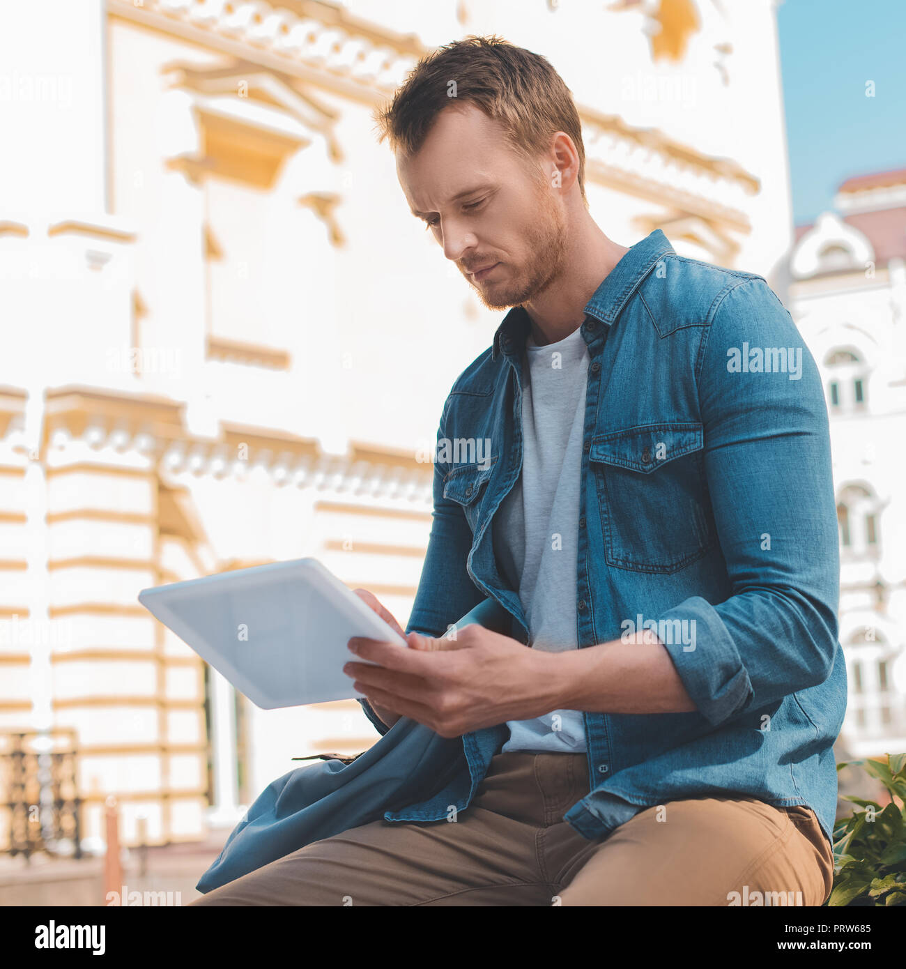 handsome young man in denim shirt using tablet on street - Stock Image