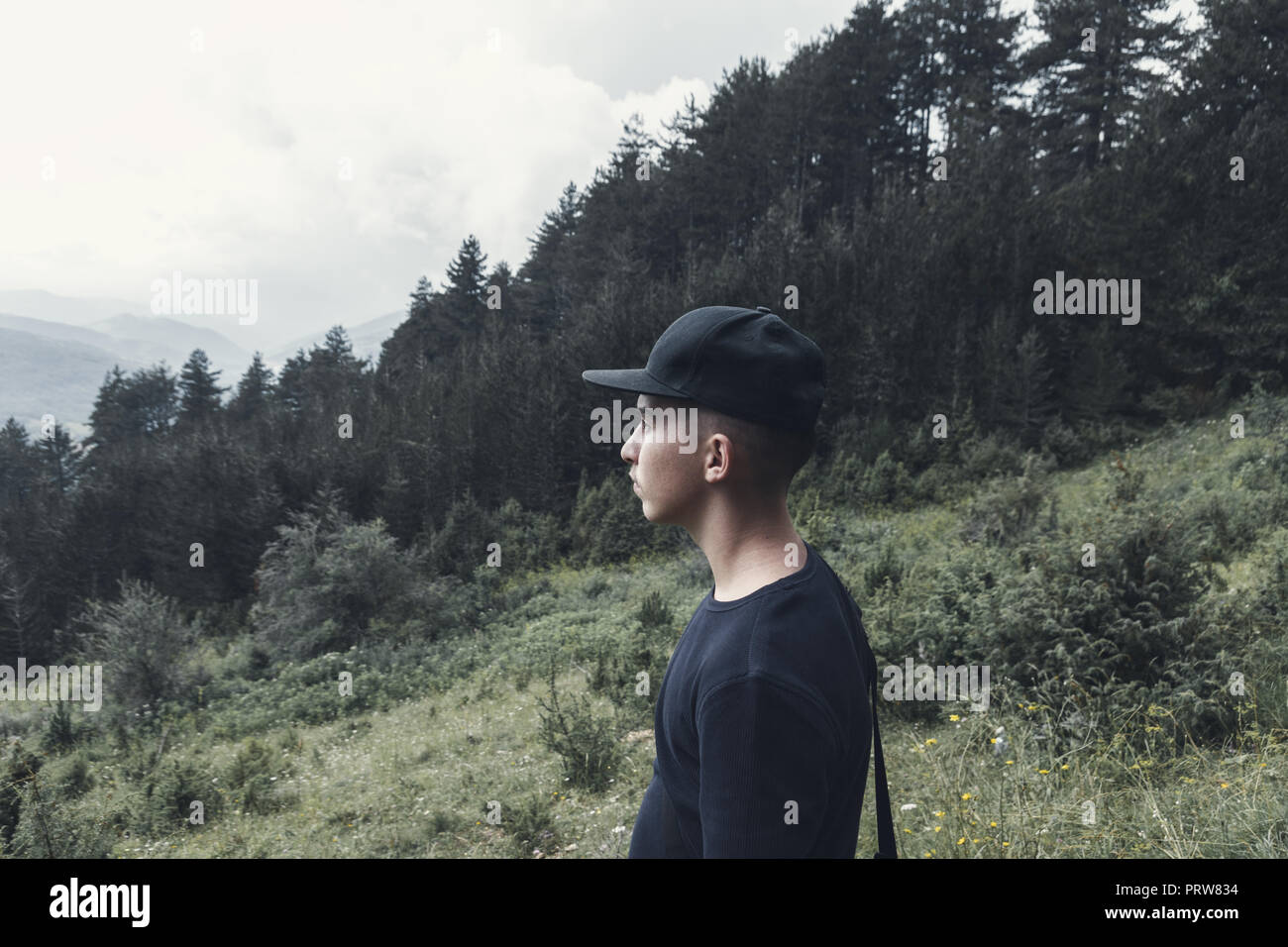 portrait of young hiker with black cap watching to the valley - Stock Image