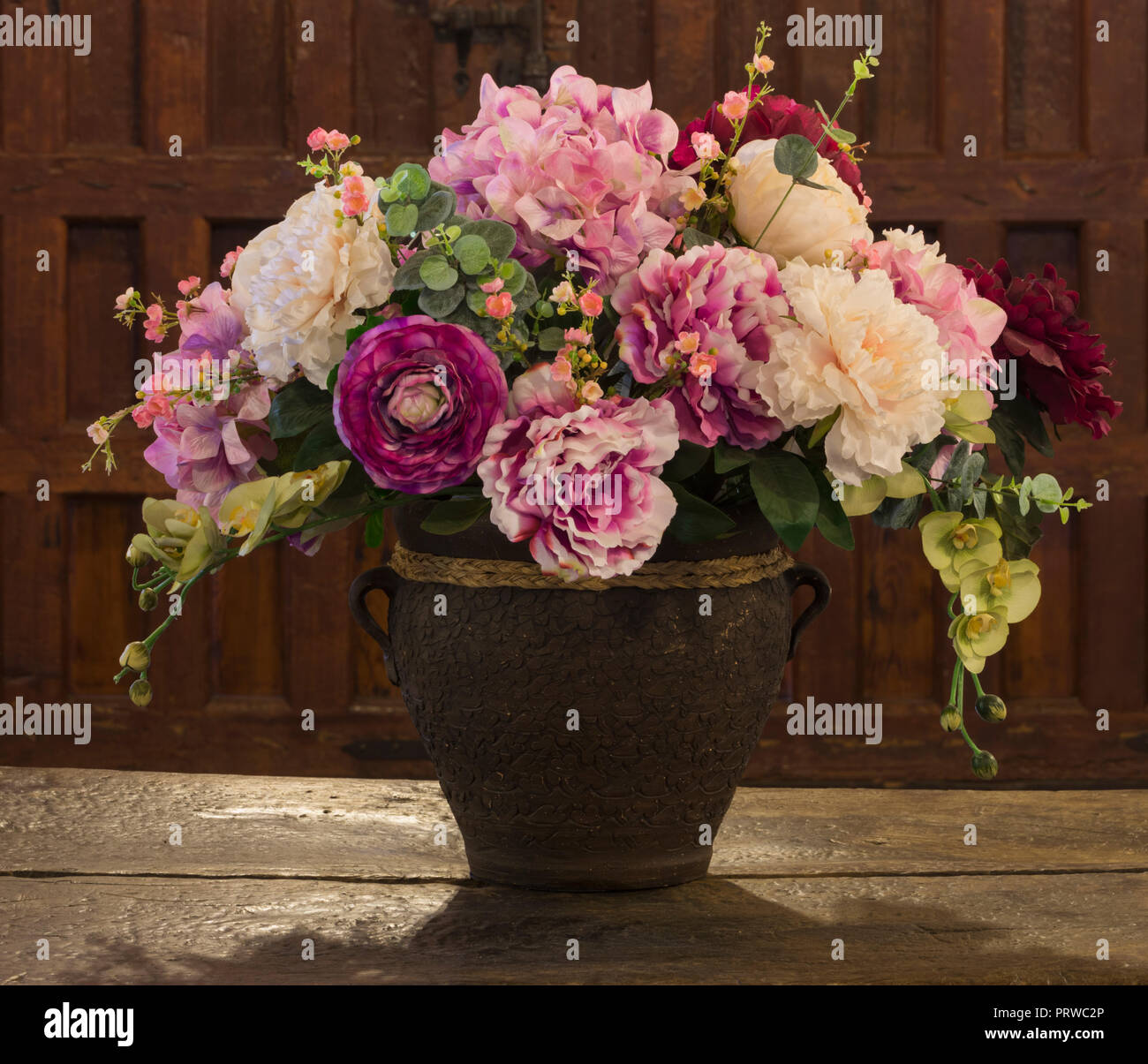 Flower arrangement in old vase on distressed table. - Stock Image