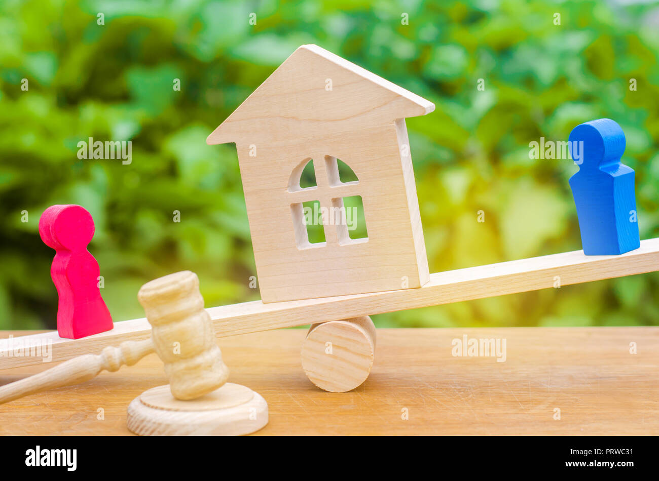 division of property by legal means. clarification of ownership of the house. wooden figures of people. man and woman are standing on the scales. tria - Stock Image