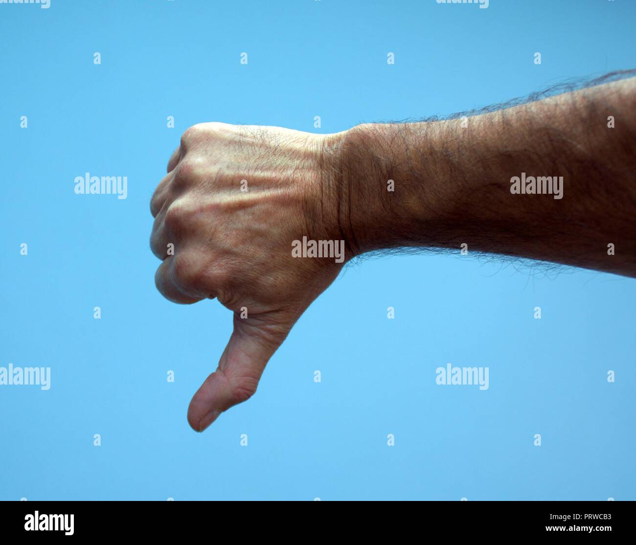 Thumbs down sign made by mans hand - Stock Image