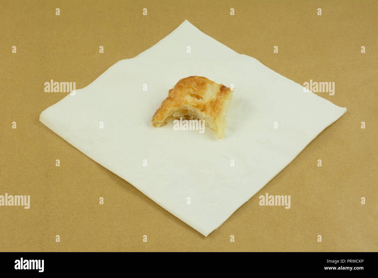 Mini apple breakfast turnover with bite eaten on white napkin on table - Stock Image