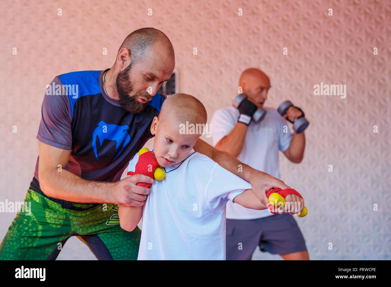 the coach teaches the boy kick Boxing. - Stock Image