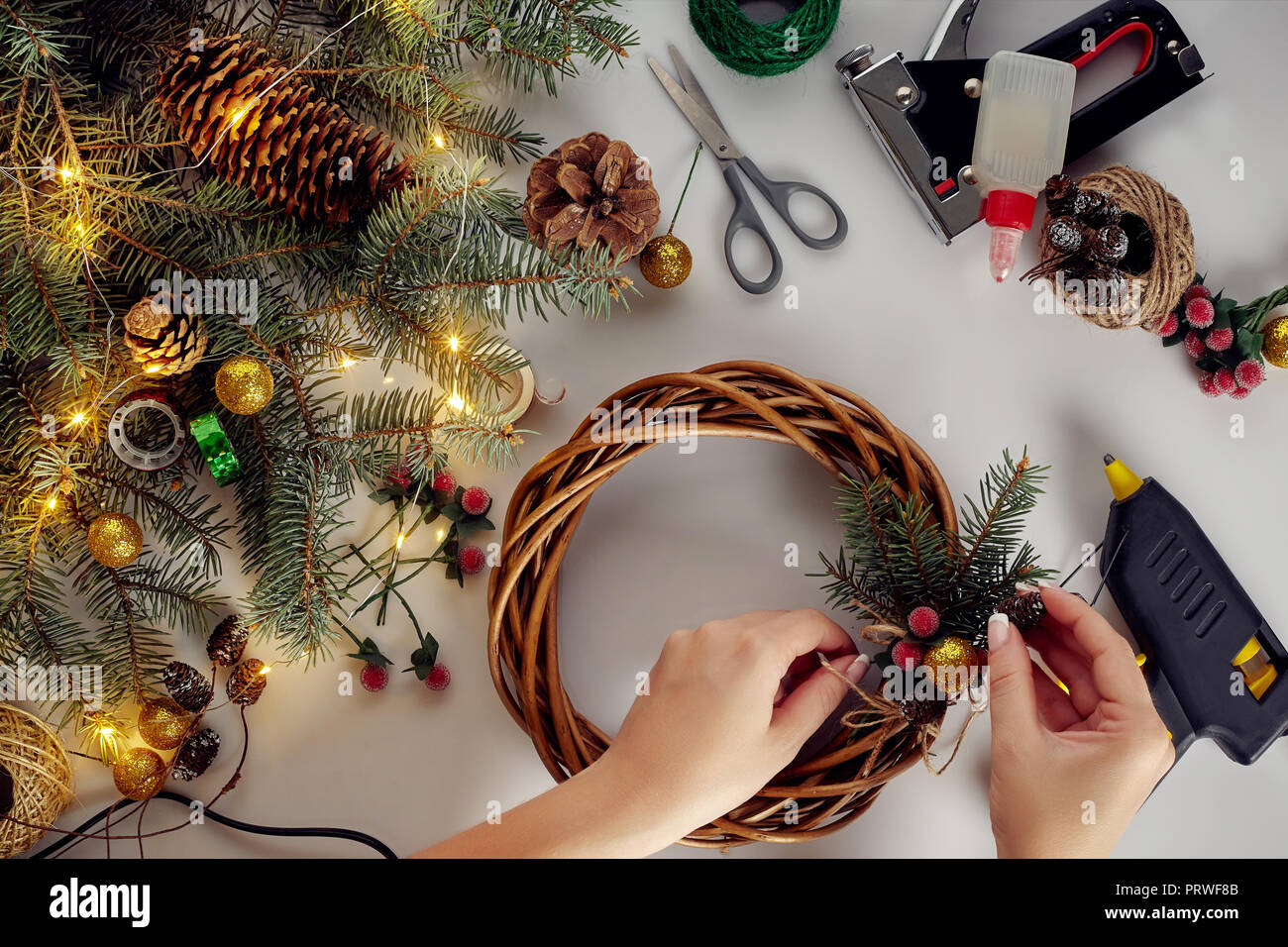 Top view of female hands make a Christmas wreath. Packed gifts and ...