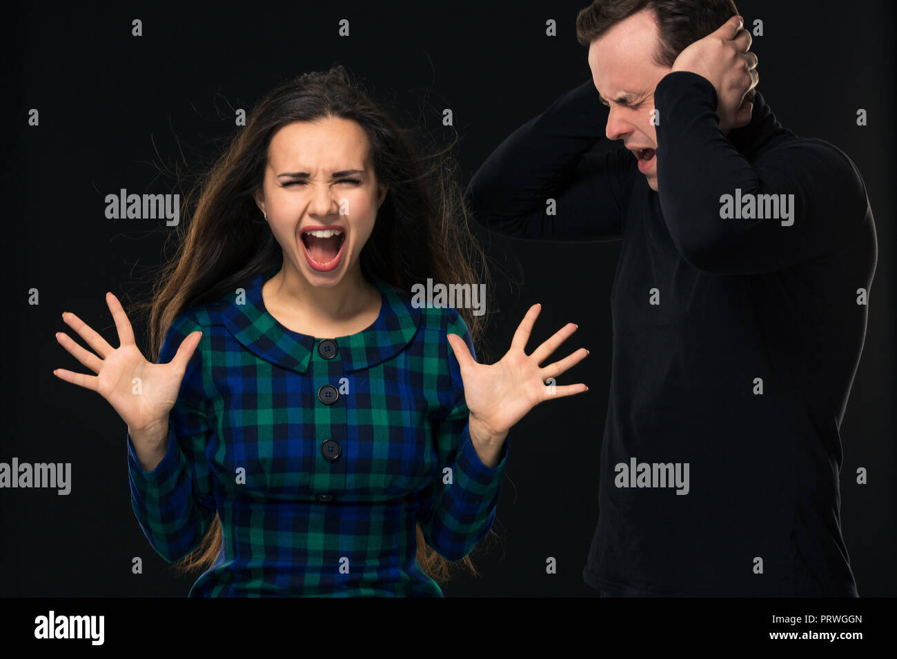 ouple having conflict, bad relationships. Angry fury woman screaming man closing his ears. - Stock Image