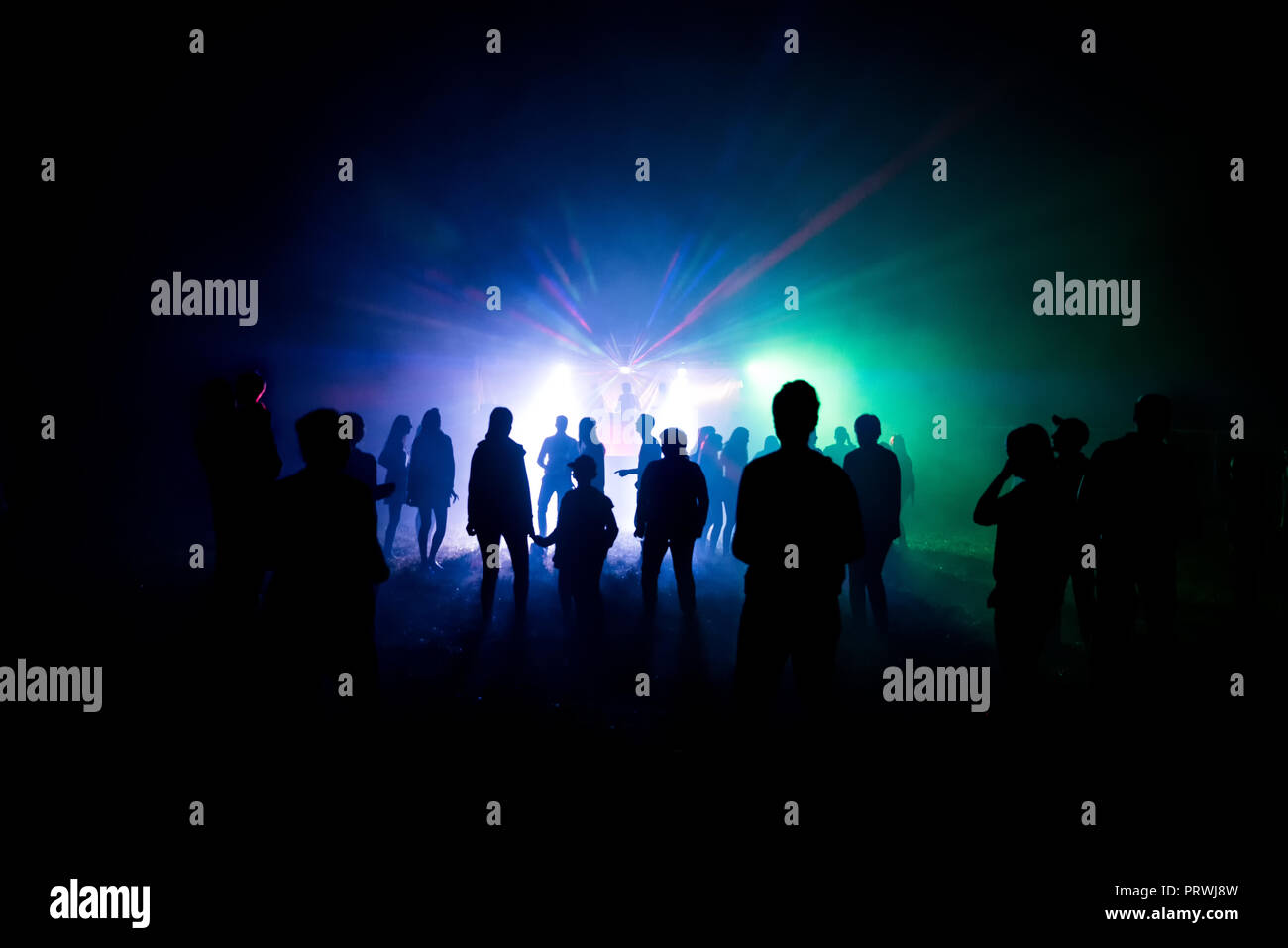 Abstract blurry background, silhouettes of people at open air party Stock Photo