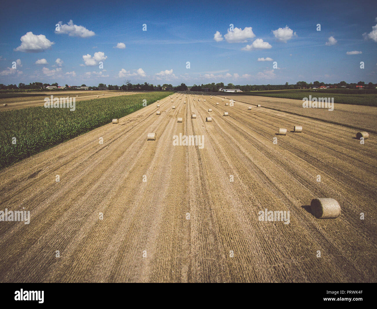 Aerial view of round hay bales on stubble under blue cloudy sky, with a distant village in the background - Stock Image