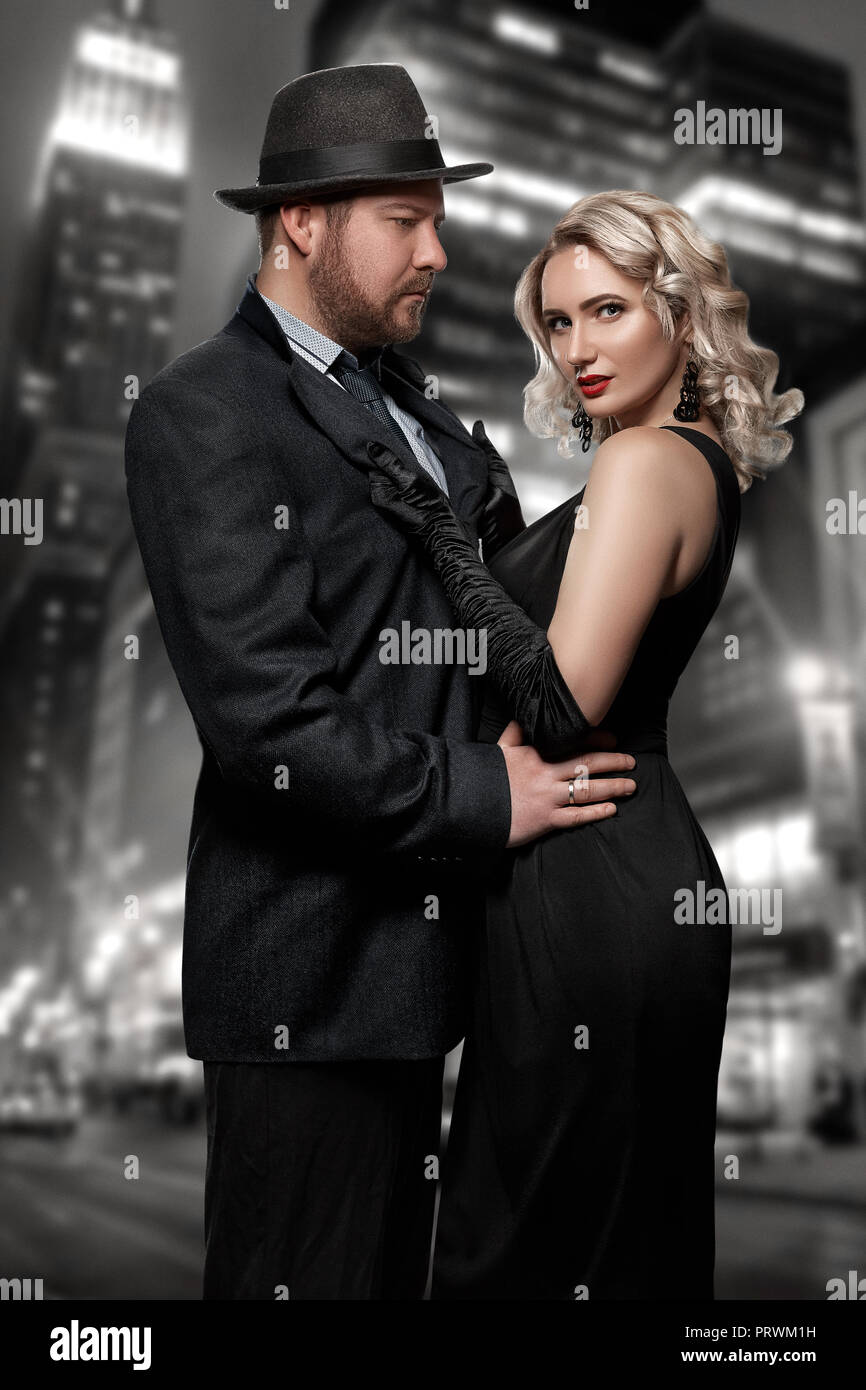 Film noir. Detective man in a raincoat and hat and a dangerous woman with red lips in black dress. Couple stands against the background of the night city - Stock Image