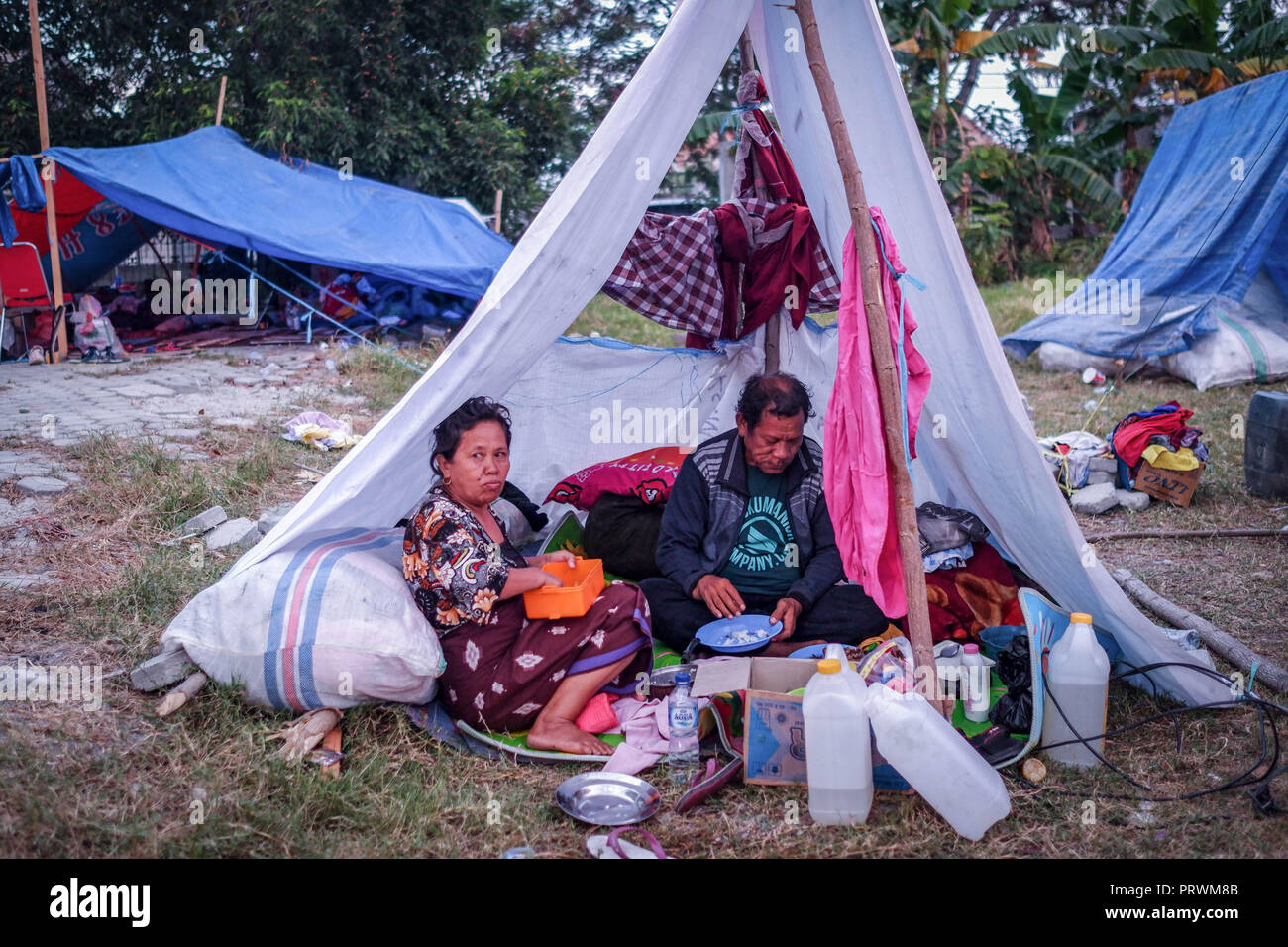 Palu, Indonesia. 13th Oct, 2018. Refugees seen resting in the Lere Refugee settlement.A deadly earthquake measuring 7.7 magnitude and the tsunami wave caused by it has destroyed the city of Palu and much of the area in Central Sulawesi. According to the officials, death toll from devastating quake and tsunami rises to 1,347, around 800 people in hospitals are seriously injured and some 62,000 people have been displaced in 24 camps around the region. Credit: Hariandi Hafid/SOPA Images/ZUMA Wire/Alamy Live News - Stock Image